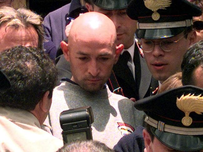 Pantani surrounded by police and media leaving his hotel after being disqualified from the Giro d'Italia for failing a blood test in 1999.