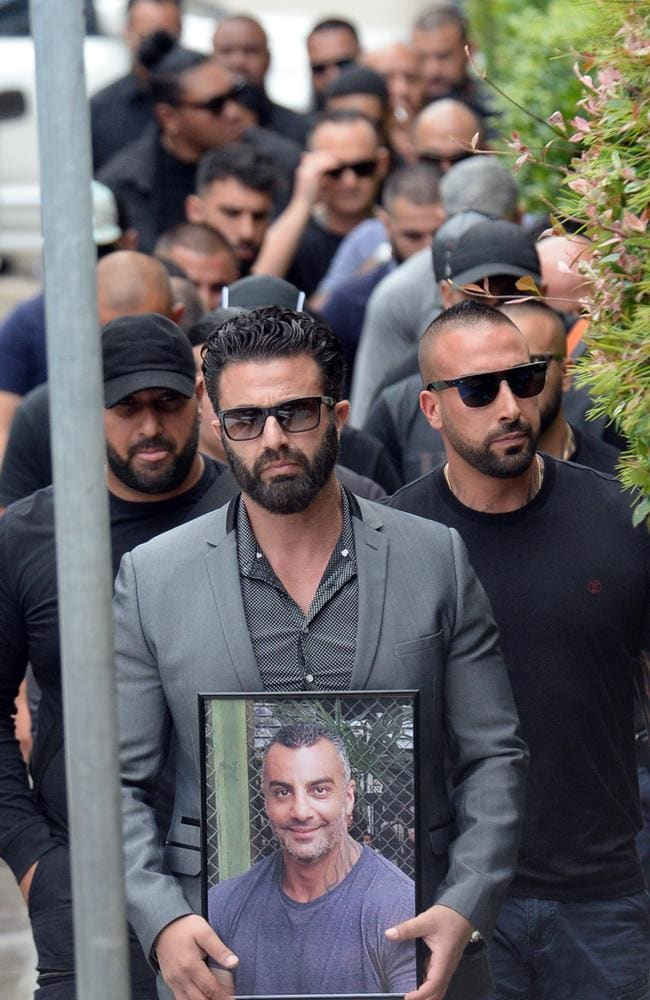 Friends file in to Mick Hawi's funeral at Al-Zahra Mosque behind a man carrying a photograph of the slain Comanchero. Picture: Jeremy Piper