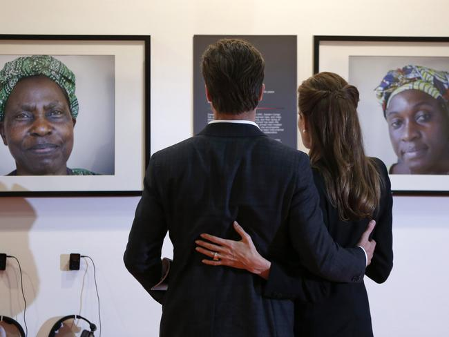 Face to face ... Jolie and Pitt look at displayed pictures of victims of violence at the Global Summit to End Sexual Violence in Conflict.