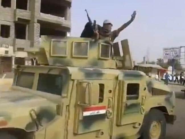 Acquisitioned ... militants from the Islamic State of Iraq and the Levant (ISIL) parading with an Iraqi army vehicle in the northern city of Beiji. Picture: YouTube/AFP