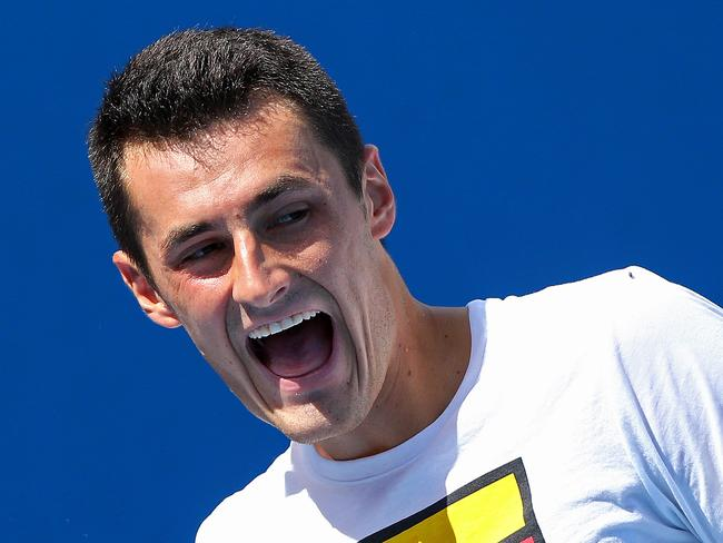 Bernard Tomic warms up for his fourth round clash against Andy Murray.