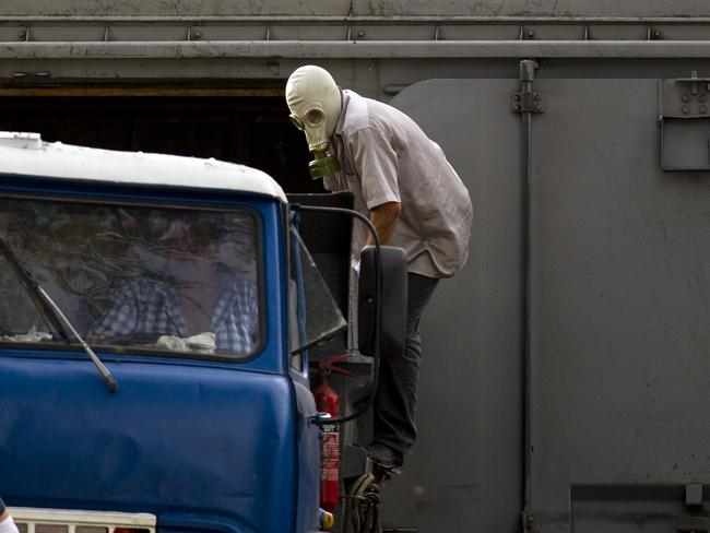 Grim work ... a man wearing a gas mask climbs on a truck unloading newly retrieved bodies from the crash site of MH17 into a refrigerated train in Torez, eastern Ukraine. Picture: Vadim Ghirda