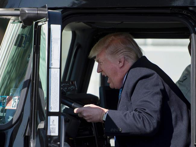 US President Donald Trump sits in the drivers seat of a semi-truck as he welcomes trucking CEOs to the White House. Photo: AFP/Jim Watson