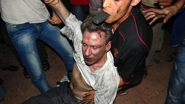 A severely wounded unidentified man is carried away by Libyan men inside the US consulate compound in the eastern city of Benghazi, early on September 12, 2012. An armed mob protesting a film deemed offensive to Islam attacked the US consulate in Benghazi late on September 11 killing a US official, hours after angry Islamists stormed Washington's embassy in Cairo. TOPSHOTS AFP PHOTO