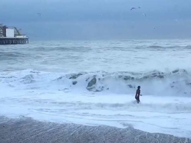 Woman runs into rough seas in Brighton to save her dog.