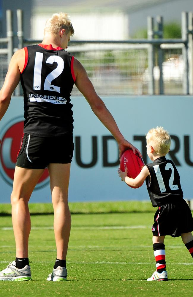 Nick Riewoldt spends some time with a young fan after training.