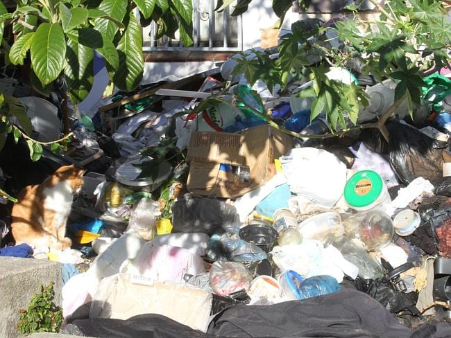 The rubbish fills the front yard of the house up to the window sills and over the front patio.