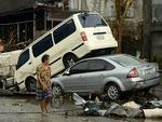 A woman walks past stacked up vehicles in Tacloban, on the eastern island of Leyte, The Philippines. Picture: AFP