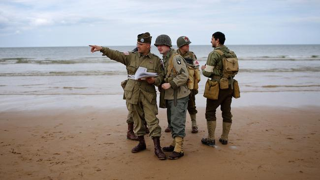 Fight them on the beaches ... re-enactors dressed as US troops prepare for the 70th anniversary of D-Day on Omaha Beach.