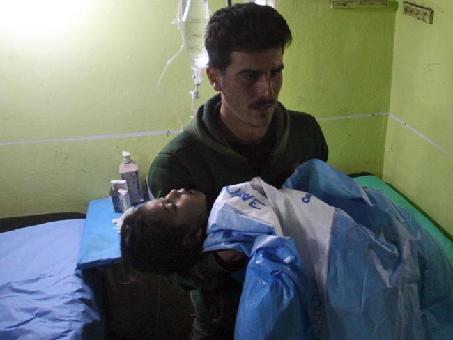 An unconscious Syrian child is carried at a hospital in Khan Sheikhun following the toxic gas attack on April 4. Picture: AFP