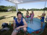 Arabella, 6, and Philippa Bromley, 3, of Moorooka, give James McMenamin a spray at New Farm Park. Pic: Annette Dew