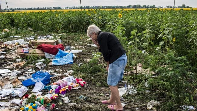 A woman is overcome with emotion as she studies debris from Malaysia Airlines flight MH17.