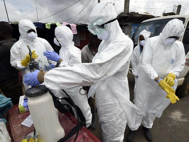 Gearing up ... Members of the Red Cross put on their protective suits as they get ready to collect the body of a person suspected of dying from the Ebola virus in the West Point district of the Liberian capital Monrovi. Pic: AFP PHOTO / PASCAL GUYOT.