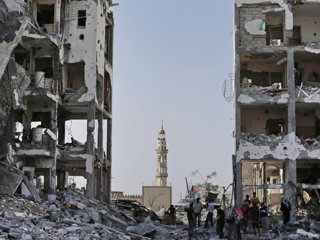 Nothing left ... Backdropped by the damaged minaret of the Al-Azba mosque, Palestinians inspect the damage to the Nada Towers residential neighbourhood in the town of Beit Lahiya, northern Gaza strip. Picture: AP
