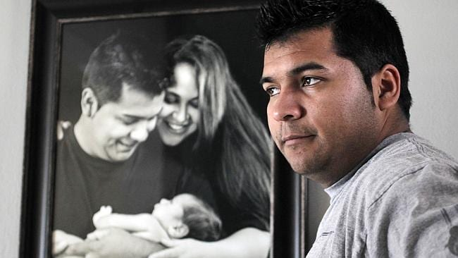 Family portrait ... Erick Munoz stands with an undated copy of a photograph of himself, left, with wife Marlise and their son...