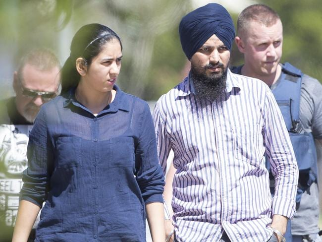Machine operator Gurjinder Girn and his wife Navjot Kaur are escorted from the scene after hiding in a building upon hearing the gun shots / Picture: Cameron Richardson