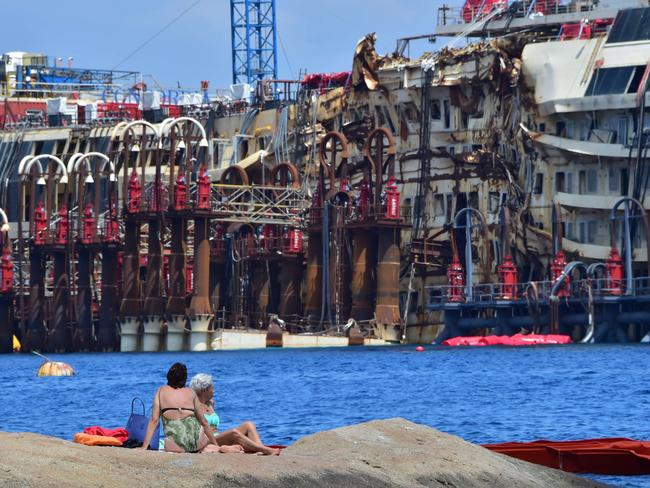 Tourist attraction ... people sunbathe on rocks at a beach on Giglio Island facing the wrecked  <i>Costa Concordia</i> cruise ship.