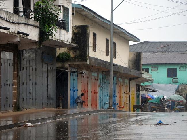Deserted ... A lone man sits outside shops that were closed in Monrovia's West Point slum as part of quarantine measures to contain the spread of Ebola. Pic: AFP/ZOOM DOSSO