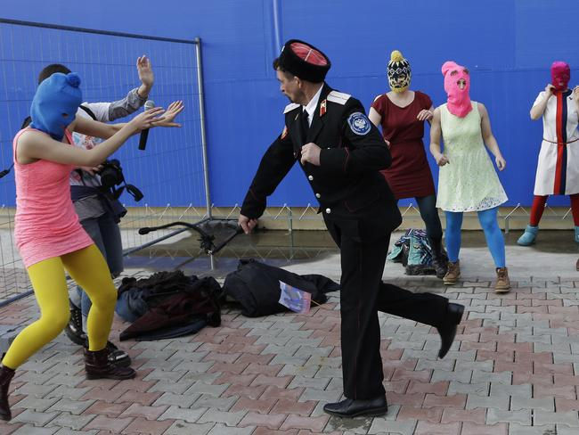 Arrested ... A Cossack militiaman attacks Nadezhda Tolokonnikova and a photographer as she and fellow members of the punk group Pussy Riot, including Maria Alekhina, centre, in the pink balaclava, stage a protest performance in Sochi. Picture: Morry Gash