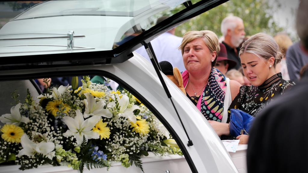 Maddison (right), the stepdaughter of Julie, pays an emotional farewell today to Julie and Hudson Bullock, who were killed in a freak car accident near Wilton. Picture: Stephen Cooper.