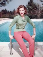 Lauren Bacall, US actress, wearing a green double-breasted cardigan and red trousers as she poses beside a swimming pool, circa 1950. Picture: Getty