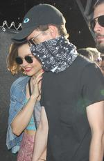 Miranda Kerr was seen with a masked Evan Spiegel at Coachella in Indio, California. The Snapchat CEO wore a black bandana over his face with black shades as he held hands with Kerr. She hid behind him as she tried to enter the polo fields. Picture: BackGrid