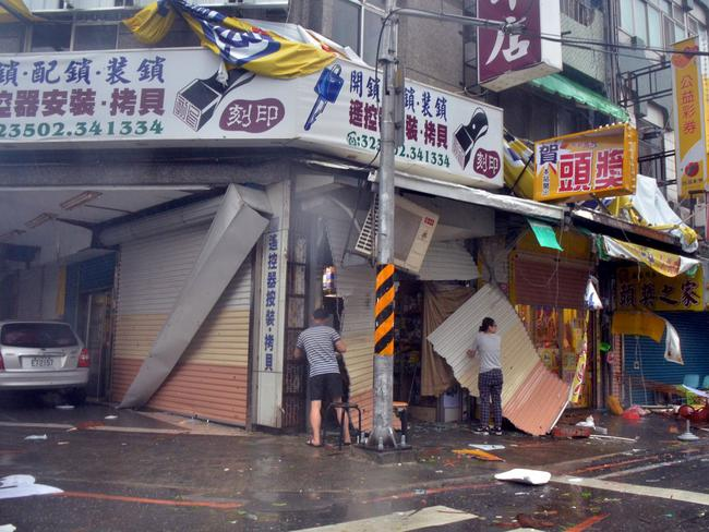 A man and a woman are seen among debris in front of a shop with broken shutters, torn away by strong winds of Typhoon Nepartak in Taitung on July 8, 2016. Picture: AFP.