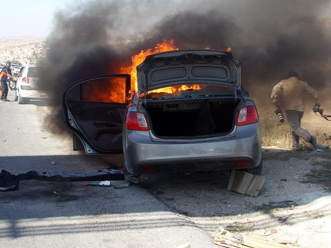 Up in flames...AFP photographer Jaafar Ashtiyeh (R) moves with his equipment away from his car as it burns after a tear-gas canister fired by Israeli soldiers landed inside the car. Picture: AFP