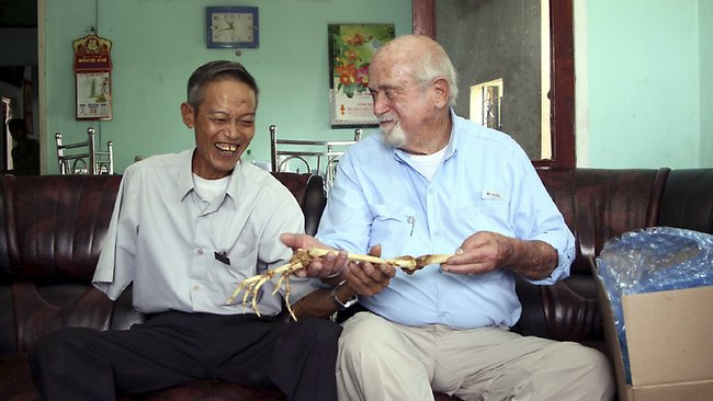 Dr Sam Axelrad, right, hands over arm bones belonging to former North Vietnamese soldier Nguyen Quang Hung, left, at Hung's house in the town of An Khe, Gia Lai province, Vietnam.