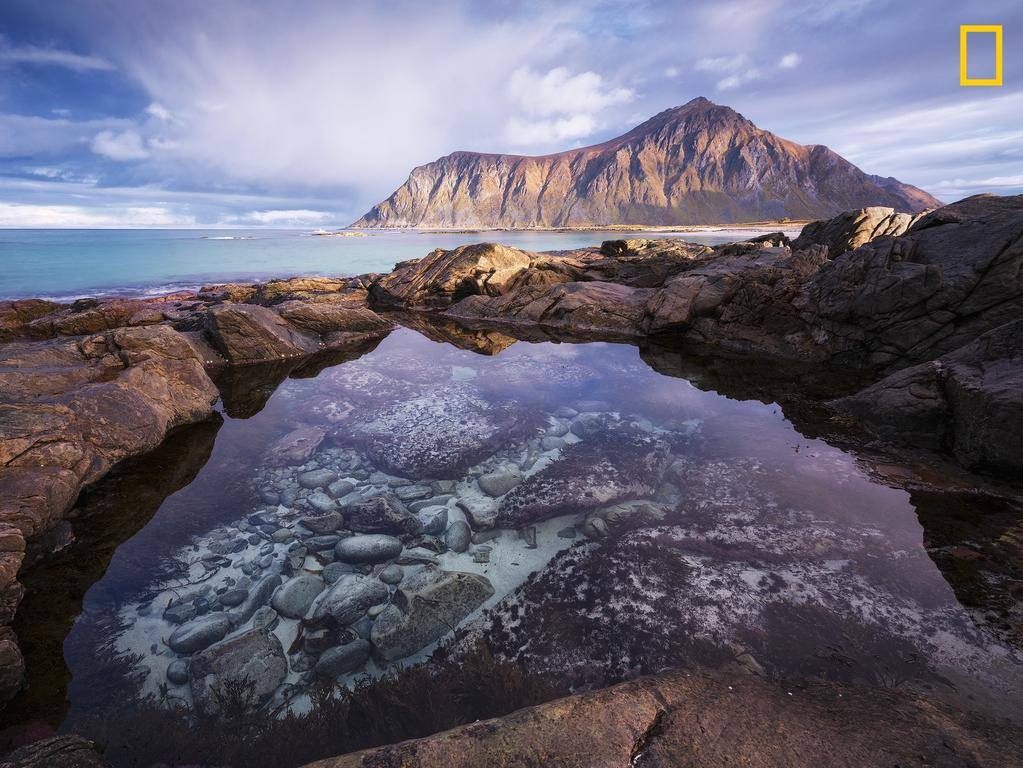 Photo by Felix Inden / National Geographic Nature Photographer of the Year contest enchanted A tidal pool at Lofoten islands in northern Norway acts as natural eye catcher. with the high tides around full moon, white sand gets washed into the pool and then the magic unfolds.