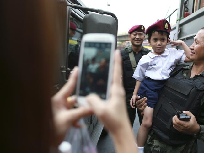 Country divided ... a mother takes photograph of her son and Thai soldiers providing security at Victory Monument in Bangkok. Picture: AP