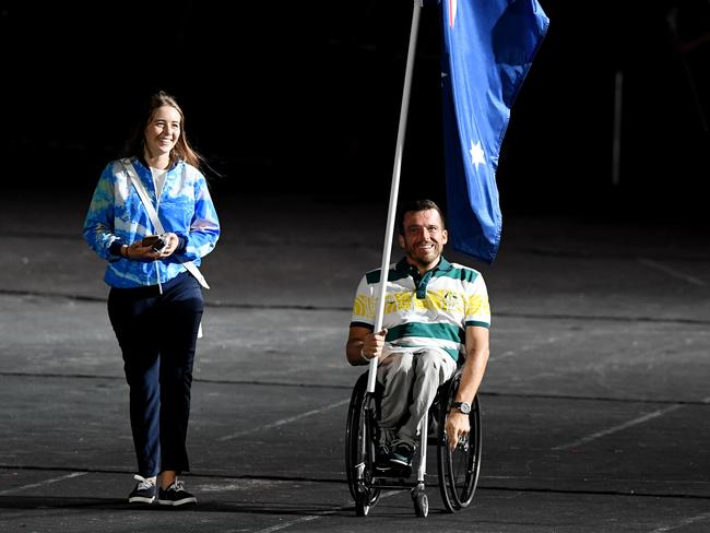 Flag-bearer Kurt Fearnley enters the stadium before the start of the closing ceremony. Picture: Darren England/AAP