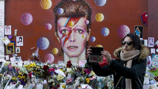 A woman takes a selfie by floral tributes placed in front of a mural of David Bowie.