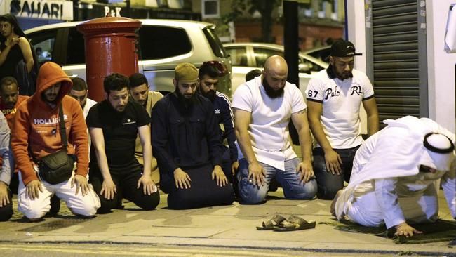 Local Muslims observe prayers at Finsbury Park where a vehicle struck pedestrians. Picture: Yui Mok/PA via AP