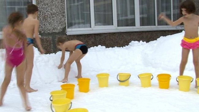 Siberian kids play in the snow, pouring a buckets of cold water over their heads in an effor to keep fit and healthy. Picture: Siberian Times