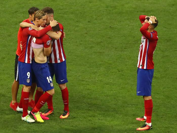 Players of Atletico Madrid console themselves.