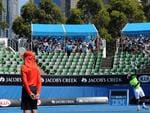 A sparse crowd gathers in limited shade as Donald Young serves to Andreas Seppi.