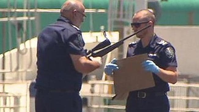 Police officers hold a rifle retrieved from the car. Pic: Seven News