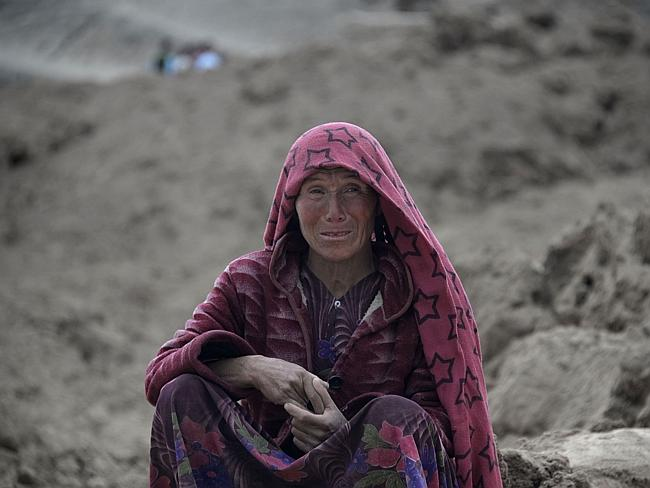 Devastated ... an Afghan villager cries as she sits on top of a mud field at the scene of the mudslide.