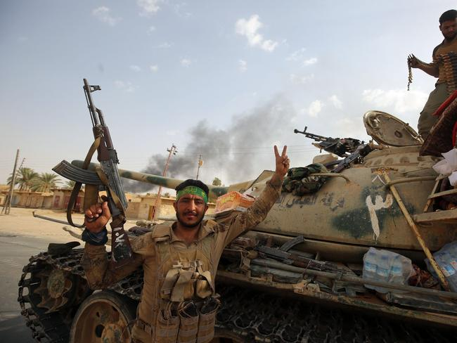 Iraqi forces and members of the Hashed al-Shaabi (Popular Mobilisation units) enter the city of al-Qaim. Picture: AFP