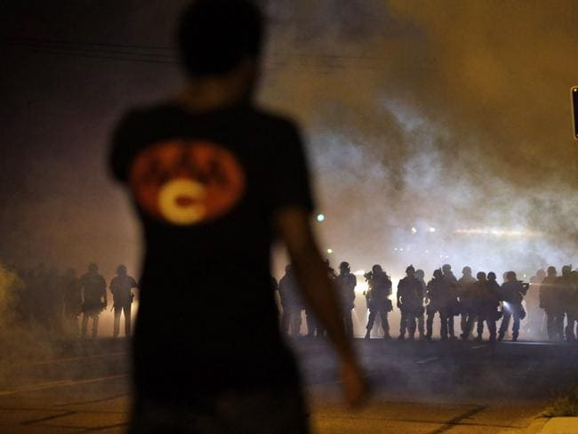 Violent clashes ... a man watches as police walk through a cloud of smoke during a clash with protesters in Ferguson, Missouri. Picture: AP