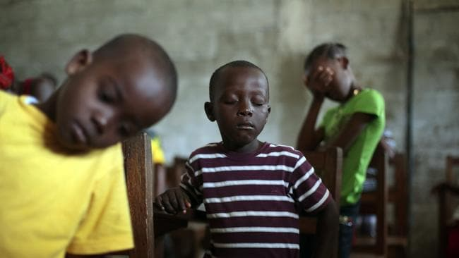 A generation hit hard ... children praying during Sunday service in Liberia last month. Photo: AP