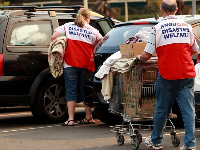 Disaster welfare volunteers help bushfire-affected residents pack donated goods into their cars.