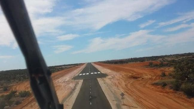 A view from the cockpit of a Royal Flying Doctor Service aircraft showing how the main road suddenly becomes a wise runway.