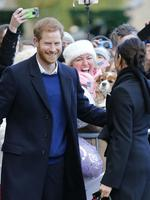 Britain's Prince Harry and his fiancee Meghan Markle meet a fan with a dog decorated with american flags as they arrive for a visit to Cardiff Castle in Cardiff, Wales, Thursday, Jan.18, 2018. Picture: AP