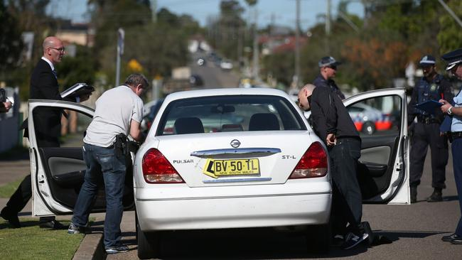 Operation ... police search a car outside a house in Guildford, suburban Sydney.