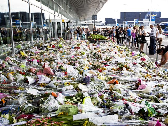 Atrocity against innocent people ... People stand in front bouquets of flowers laying in tribute of the victims of downed Malaysia Airlines flight MH17 at the Schiphol Airport, near Amsterdam.