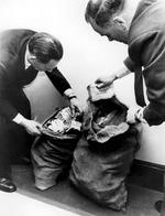 Two unidentified officers look inside two sacks filled with 50,000 pounds, part of the money that was stolen in the robbery of the Royal Mail train in 1963. Picture: AP Photo