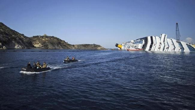 Small boats of the Italian Navy pass by the stricken cruise liner Costa Concordia lying aground in front of Giglio island on January 23, 2012 after hitting underwater rocks on January 13. Picture: AFP PHOTO / FILIPPO MONTEFORTE