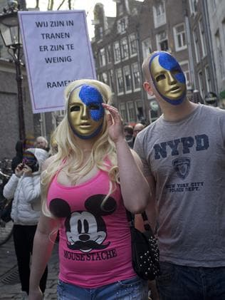 "A banner reads ""We Are in Tears, There's To Few Windows"" as a group of masked prostitutes and sympathisers take to the streets in Amsterdam. Picture: Peter Dejong"